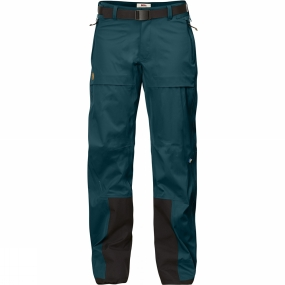 Fjallraven Wind and waterproof three-layer shell trousers for year-round use in changeable weather conditions. Made from stretchy Eco-Shell for high performance and the lowest possible environmental impact. The fabric is hardwearing at the same time as it follows body movements and ventilates out moisture that builds up inside when you are active. A perfect choice for trekking and summit touring in difficult terrain - the minimalistic design makes moving forward easier while you have complete protection from the elements. The cut is carefully thought through and pre-shaped knees and rear give maximum freedom of movement. The cut is adapted so they can be worn over a pair of trekking trousers made from G-1000, for example. Long two-way waterproof zips at the sides release excess heat and make putting on/taking off easy. The waist has a hook and loop adjustment at the side and a belt with an easy-to-handle flat buckle that sits well under a climbing harness or backpack hipbelt. Two pockets with zips keep small items close at hand. Cordura reinforcements at the hems and on the inside lower legs protect against wear from boots and crampons. At the bottom there is a button and a hidden drawstring to adjust the width of the legs. Eco-Shell is a waterproof, breathable and sustainable hardshell fabric that is treated with fluorocarbon-free impregnation. Eco-Shell is made from recyclable polyester, and all emissions during production and transport are climate compensated.
